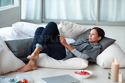 Buy stock photo Young woman reading while lying on the floor
