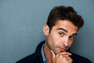 Buy stock photo Studio portrait of a handsome young man with his hand on his chin