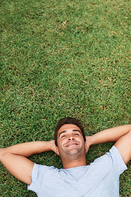 Buy stock photo Handsome man laying on the grass with hands behind head