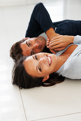 Buy stock photo Attractive couple lying on the floor smiling