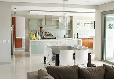 Buy stock photo View of a woamn through an open plan lounge, dining room and kitchen in a modern style