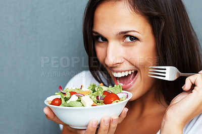 Buy stock photo Woman holding bowl of salad against blue background