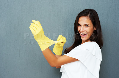 Buy stock photo Pretty woman wearing dish gloves against blue background