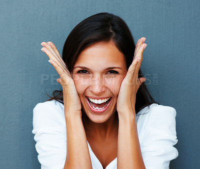 Woman laughing with hands against cheeks