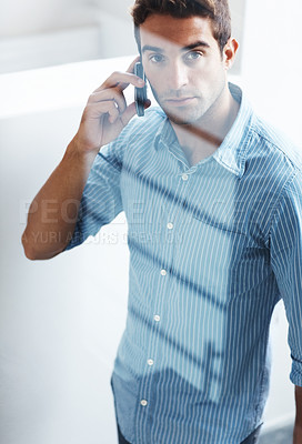 Buy stock photo Portrait of a young man talking on a mobile phone
