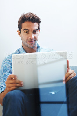 Buy stock photo Shot of confident young man sitting behind a glass window and working on a laptop