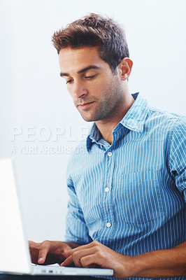 Buy stock photo Shot of a handsome young man using laptop