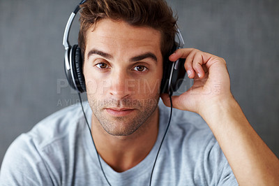 Buy stock photo Closeup portrait of a smart young guy listening to music on headphone against grunge background
