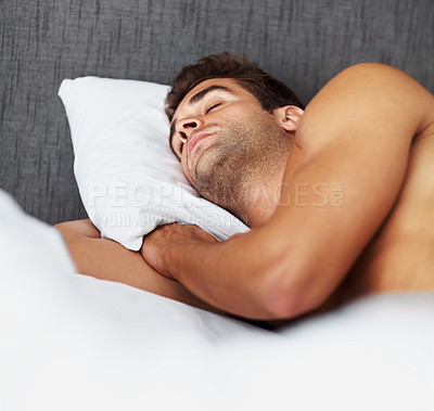 Buy stock photo Shot of a shirtless young man sleeping in bed at home