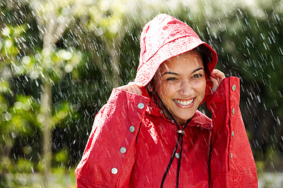 Buy stock photo An excited young female holding a red raincoat hat on head - Outdoors