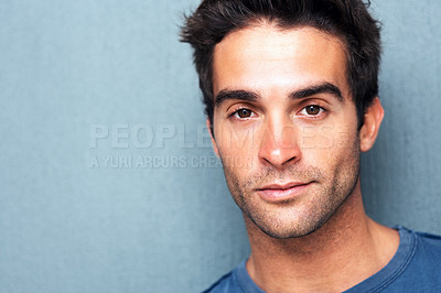 Buy stock photo Head shot of serious man gazing at the camera against a blue background - copyspace