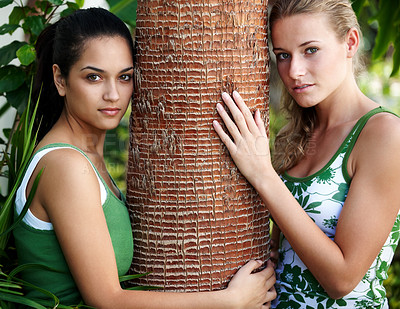 Buy stock photo Portrait of two beautiful teenage women holding a tree bark in a park - Outdoor