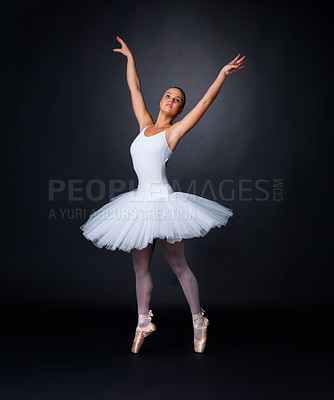 Buy stock photo Full length of a young and beautiful ballerina performing against black background