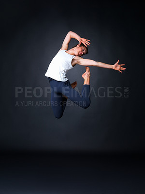 Buy stock photo Full length of a male ballet dancer jumping high against black background