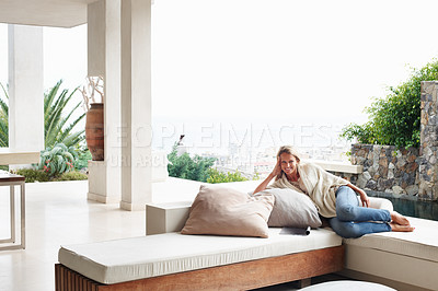 Buy stock photo Portrait of a happy mature woman relaxing on couch in a modern house