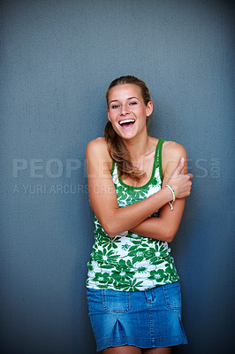 Buy stock photo Portrait of  pretty excited young woman standing against grey background and laughing