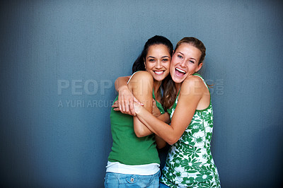 Buy stock photo Friendship - Two best girlfriends hugging eachother against grey background