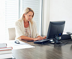 Busy mature female executive at work desk using computer