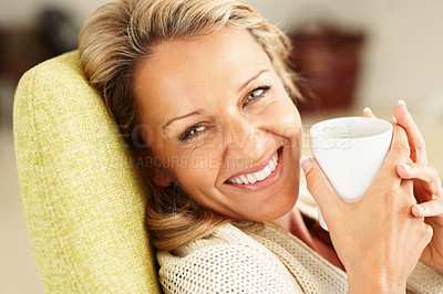 Buy stock photo Closeup shot of a cheerful middle aged woman with a cup of tea or coffee smiling