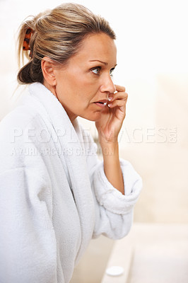 Buy stock photo Portrait of a mature woman looking at herself in the mirror