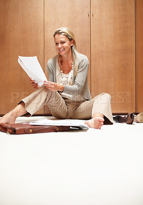 Buy stock photo Portrait of a casual mature woman sitting on floor and doing paperwork