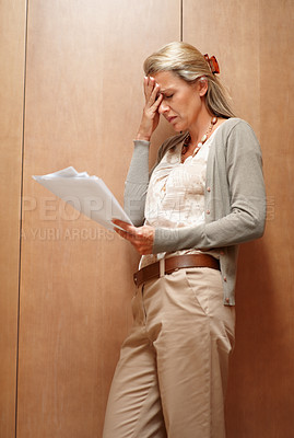 Buy stock photo Portrait of a worried mid adult woman reading a document