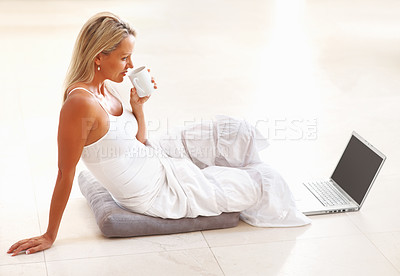 Buy stock photo Side view of a mature woman drinking tea and using laptop on floor