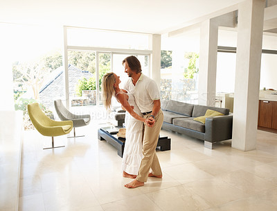 Buy stock photo Loving mature couple dancing in a spacious modern living room