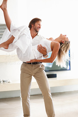Buy stock photo A romantic happy mature man carrying a woman in his arms at home