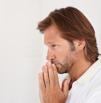 Buy stock photo Side view closeup of a mature man in deep thought against plain background, hands joined