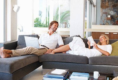 Buy stock photo Mature couple sitting on sofa at home - she reads a book, he works on laptop