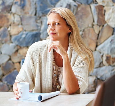 Buy stock photo Mature woman contemplating over something while reading magazine and drinking coffee