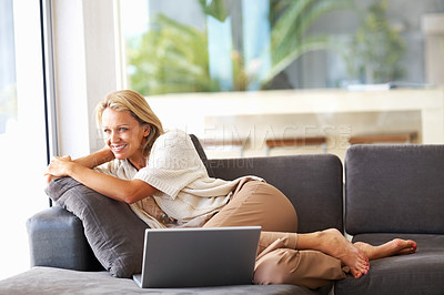 Buy stock photo Portrait of a pretty relaxed middle aged woman with laptop on couch , looking away