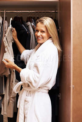 Buy stock photo Portrait of a happy mature woman selecting clothes near wardrobe after a bath