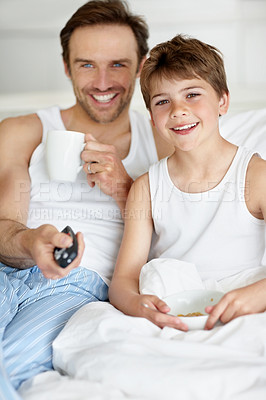 Buy stock photo Portrait of a happy father and son having breakfast on bed and watching television
