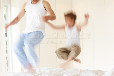 Buy stock photo Portrait of a young man and his small boy jumping on bed - Motion blurred