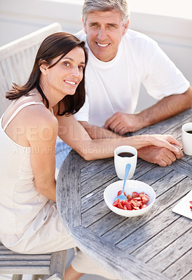 Buy stock photo Portrait of a happy middle aged couple sitting together and having breakfast together