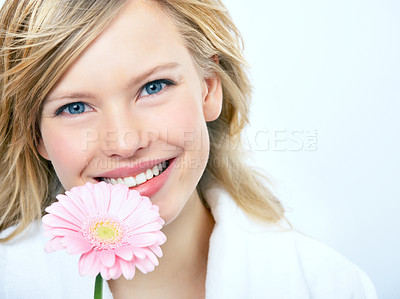 Buy stock photo Portrait of a fresh young woman holding a flower and smiling brightly at you, isolated on white - copyspace