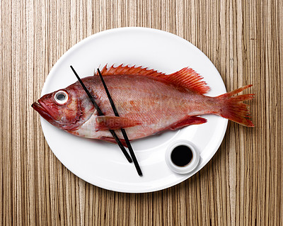 Buy stock photo Slightly humorous dish. Red raw fish on a plate.