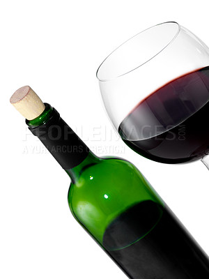 Buy stock photo A glass of red wine with a half full bottle in the background