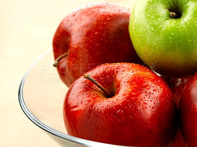 Buy stock photo Shot of a single green apple standing out amongst a bowl of red apples.