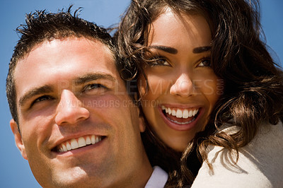 Buy stock photo Close up of a smiling couple in love. Woman hugging the man, blue sky as background.