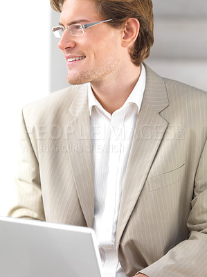 Buy stock photo Cheerful young businessman with laptop and looking away. Working in an urban city setting.