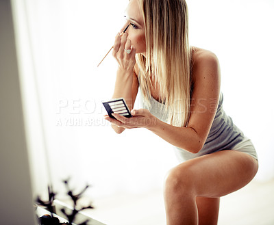 Buy stock photo Shot of a beautiful woman doing her makeup at home