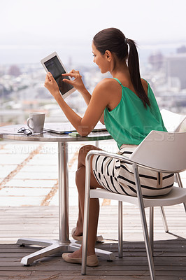 Buy stock photo Raer view shot of a young woman using a digital tablet outdoors