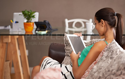Buy stock photo A beautiful woman relaxing on the couch with her digital tablet