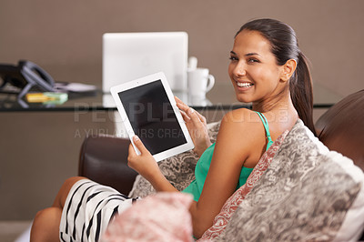 Buy stock photo A smiling young woman holding a digital tablet at home