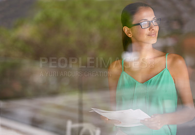 Buy stock photo A young woman looking out of her office window