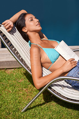 Buy stock photo A young woman relaxing with a book while sitting beside a swimming pool