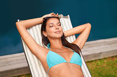 Buy stock photo A beautiful young woman relaxing in a lounge chair by a swimming pool